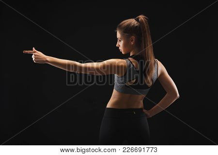 Back View Of Sporty Young Woman Pointing Away With Finger. Studio Shot On Black Background, Low Key,