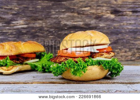 Two Homemade Grilled Hamburgers With Beef, Onion, Tomato, Lettuce And Cheese. Fresh Burger Closeup O