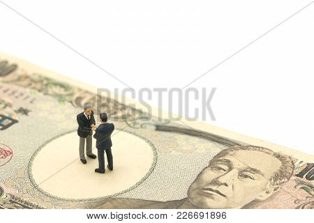 Miniature 2 People Businessmen Shake Hands Stand On Japanese Banknotes Worth 10,000 Yen Using As Bac