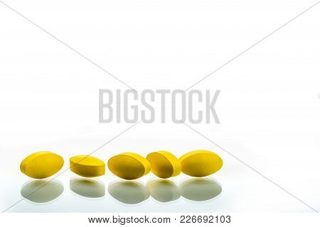 Yellow Oval Tablet Pills With Shadows On White Background With Beautiful Creative Pattern And Copy S