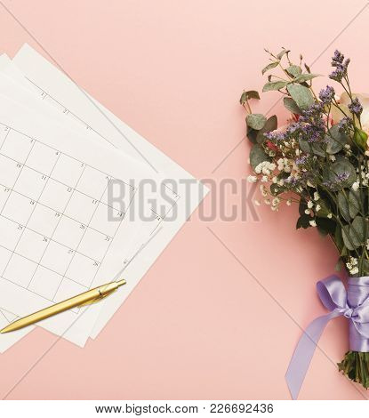 Wedding Background With Calendar. Paper Planners On Pink Table With Cute Bride Bouquet, Top View, Co