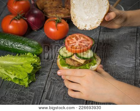 The Girl Completes The Preparation Of A Delicious Homemade Hamburger With Meat And Vegetables. Cooki