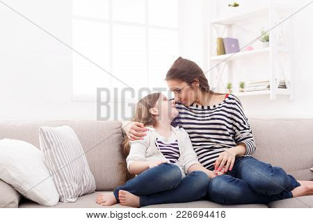 Mother With Her Cute Little Daughter Sitting On The Sofa. Mothers Day, Relationship, Motherhood, Joi