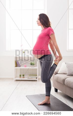 Pregnant Woman Stretching Legs Training At Home. Expectant Female Makes Warmup Aerobics Exercise, He