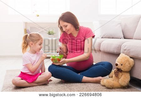 Little Girl And Her Pregnant Mom Eating Salad Sitting On Floor At Home. Motherhood, Healthy Eating A