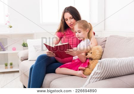 Little Girl And Her Mom Reading Book Sitting On The Sofa At Home. Mother And Daughter Study Fairy Ta