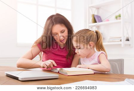Mother Helping Her Daughter With Homework. Little Girl Study Reading With Mom At Home. Motherhood, J
