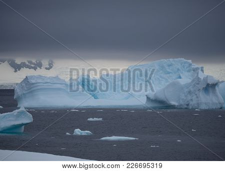 A Large Iceberg With Fissures And Ridges Floating In Charlotte Bay In Antarctica. Dense Clouds Are O