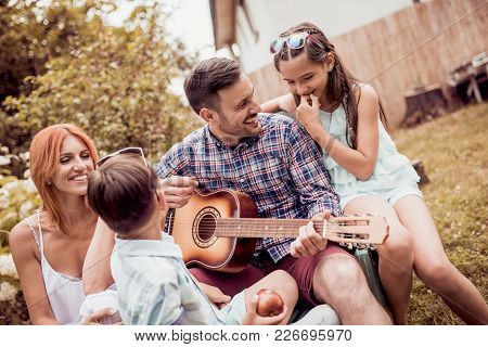 Dad Playing Guitar For The Family.