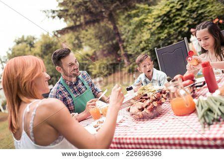 Happy Family Having Lunch In The Garden.
