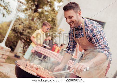 Dad Make Barbecue In The Backyard,everyone Is Having Fun.