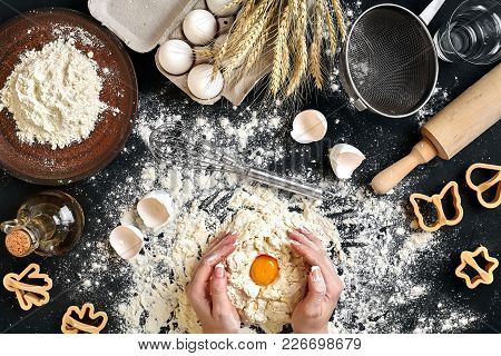 Woman Smashes An Egg Using Knife While Kneading A Pastry. Studio Shot. Top View. Ingredients For The