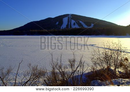 Pleasant Mountain Bridgeton Maine, Oldest Ski area in Maine.  Moosehead lake in foreground. poster
