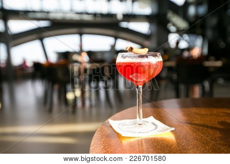 Red Cocktails With Pomegranate, Orange, Cinnamon, Black Peppercorn With Luxury Restaurant Background