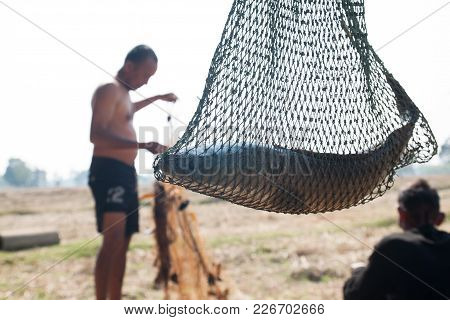 Fish In Fishing Net With The Fisherman On Background