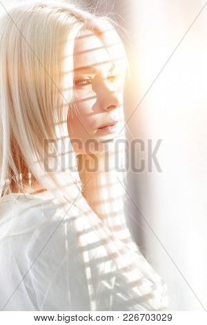 Close-up of a pensive young business woman looking out the window
