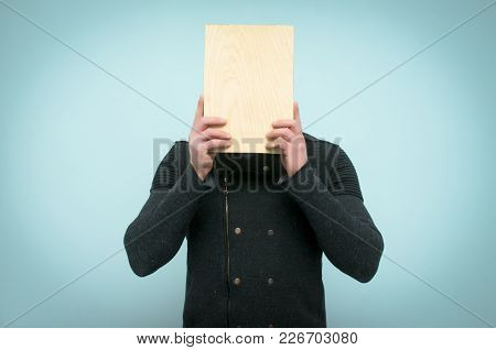 Man Hides His Face Behind A Wooden Plate With Copy Space In His Hands Isolated On Blue Background.
