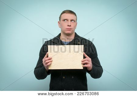 Dissapointed And Disgruntled Man Holding In Hands In Front Of Him A Wooden Board Plate With Copy Spa