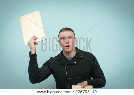 Surprised Shocked Man Is Holding In Hand Above A Head A Blank Empty Wooden Board With Copy Space For