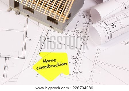 House Under Construction And Rolls Of Electrical Diagrams For Use In Engineer Jobs, Building Home Co