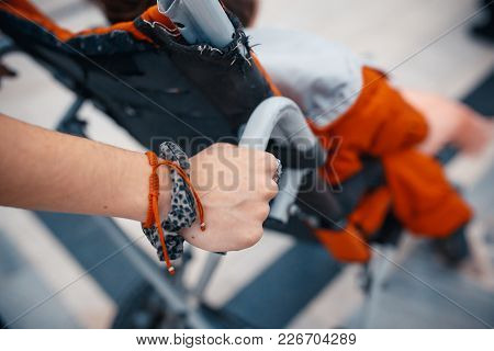 Close Up View Of The Hands Of A Woman Pushing A Disabled Man In A Wheelchair