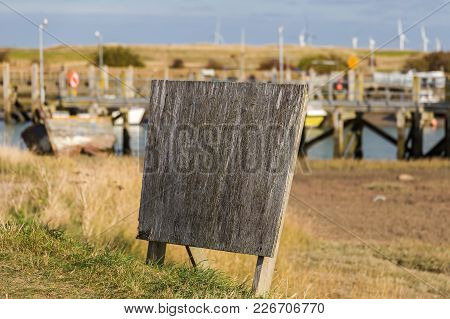 Unused Signpost With Some Boats In The Background At Rye Harbour, East Sussex, Uk