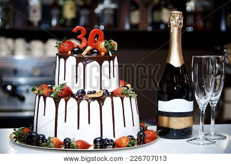 A Two-tiered White Cake With Fresh Fruit And Chocolate Stands Next To A Bottle Of Champagne And Two