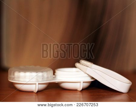 Contact Lenses In Case On Wooden Table