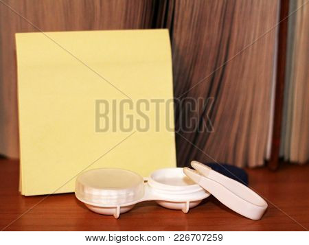 Contact Lenses In Case And Yellow Paper