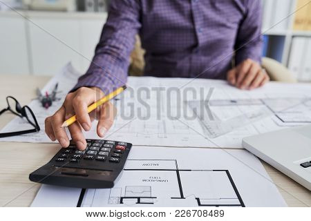 Close-up Image Of Architect Using Calculator When Working On Construction Project