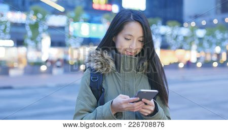 Woman use of cellphone in city at night