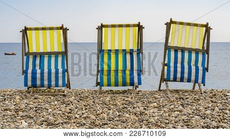 Empty Deck Chairs On The Pebble Beach In Beer, Devon, Uk - Looking At Seaton Bay And The British Cha