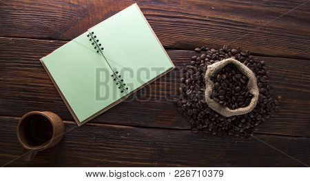Seeds Of Coffee, A Cup Of Notebook On A Wooden Background Top Viev