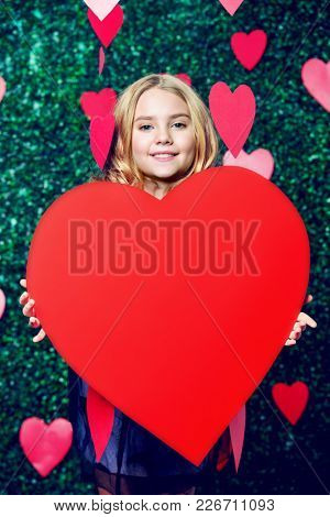 Happy pre-teen girl holding red heart surrounded by little hearts over lawny background. First love. Valentine's Day.