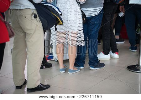 Queue Of Asian People Waiting At Boarding Gate At Airport. Closeup.