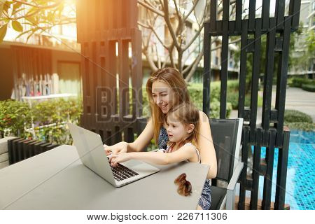 Happy Parent Mother And Daughter Working Together Use Laptop On Background Of Swimming Pool On Sunny