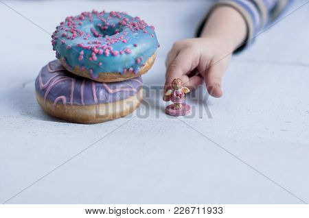 Child Takes R A Small Statuette Of Aangel Near Two Donuts With Pink And Blue Glaze Lie On Top Of Eac