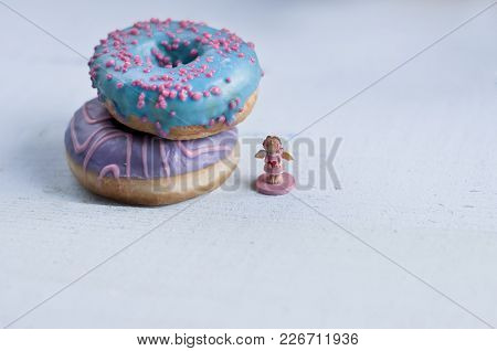 Two Donuts With Pink And Blue Glaze Lie On Top Of Each Other With Small Angell Statuette Holds Heart