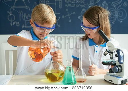 Children Mixing Various Liquids And Reagents At Chemistry Class