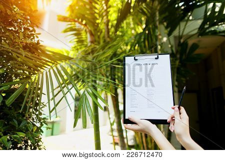 Focus On Document, Girl Fills Out Visa Application Form Against Background Of Palms And Sun And Is G