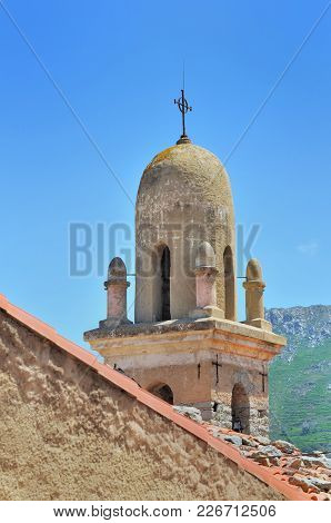 Top Of A Bell Tower Of Church Seen Of Roof Of A Corsican Village
