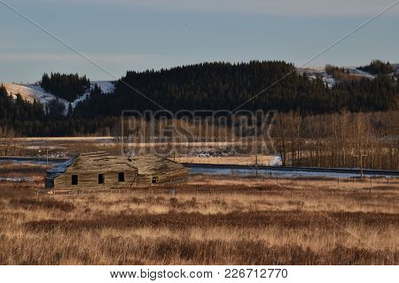 Abandoned Homestead On A Golden Field With A Railway