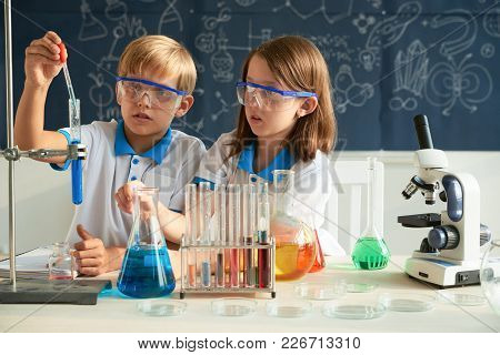 Curious Children In Goggles Doing Research At Chemistry Class
