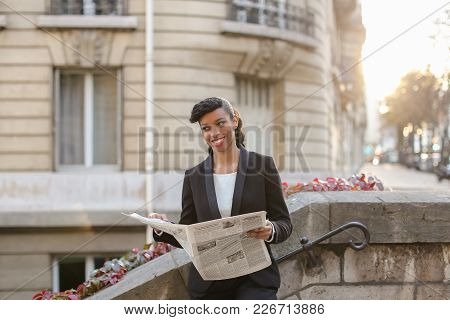 Mix Blood Journalist Reading Article In Newspaper Near High Building. Young Lady Wears Clothes In Cl