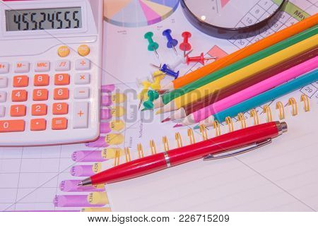 The Documents Painted Colorful Graphics. Above Lies The Pen, Pencil, Magnifier And Calculator. Busin