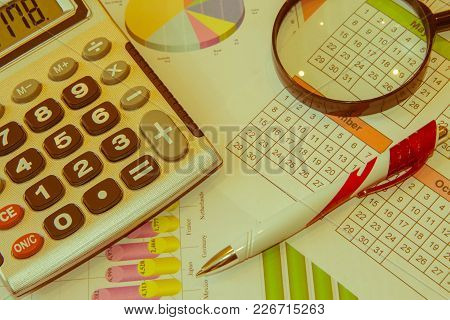 Business Accessories And Graphics, Tables, Charts On A Wooden Office Desk. Sales Earning Chart