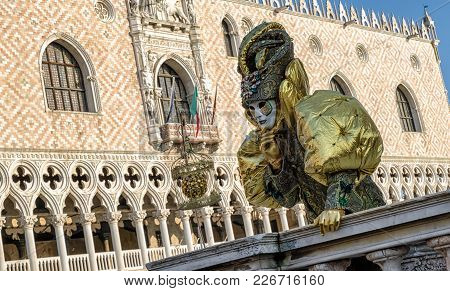 Person In Mask At The Carnival Of Venice 2018. Doge's Palace At Background