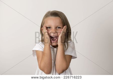 Portrait Of 7 Years Old Sweet Little Girl With Mouth Open Screaming Surprised Or Scared Holding His