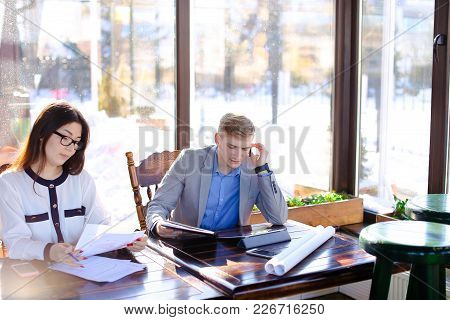 Sales Manager Talking With Client By Hands Free Phone And Working At Cafe With Female Secretary. You