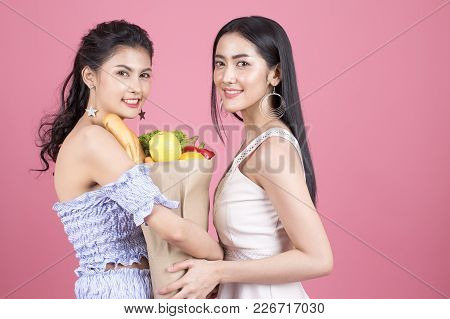 Happy Two Asian Woman Holding Groceries Bag. Isolated On Pink Background. People With Shopping Conce